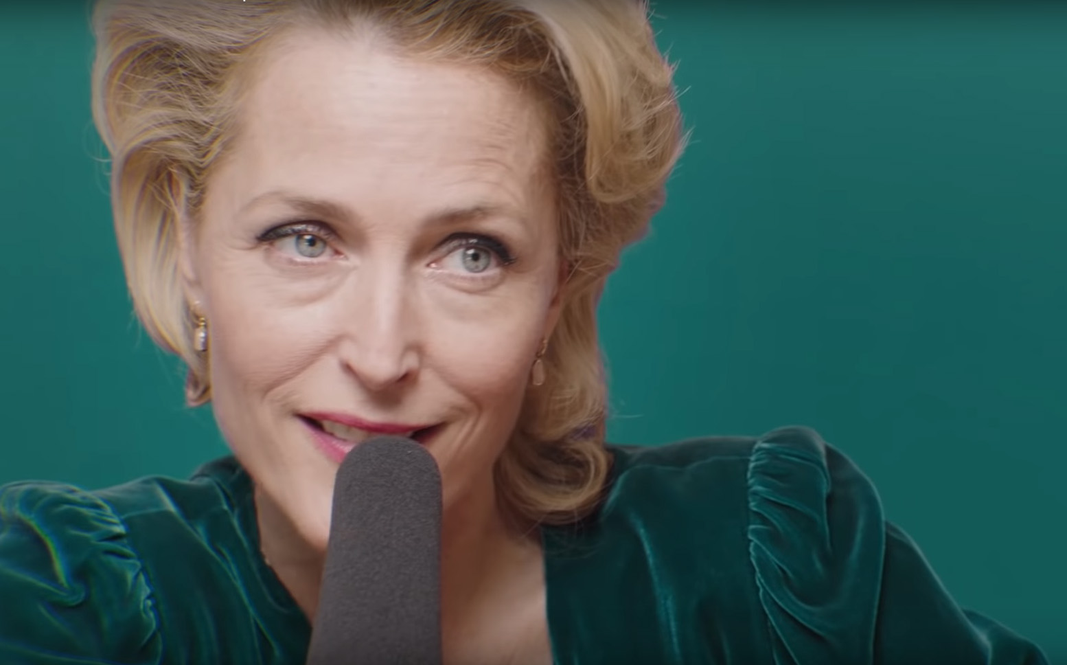 Gillian Anderson sits behind a large microphone