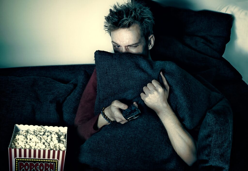 Man hiding behind pillow watching scary movie