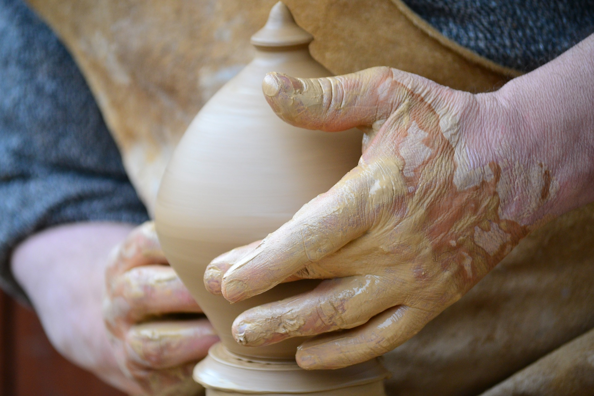 a man's muddy hands around a nearly finished pot on a wheel