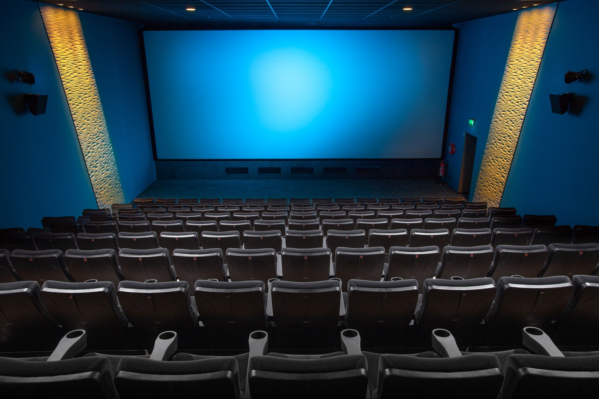 A small movie theater lit in blue with bold panels on the side walls   gtg