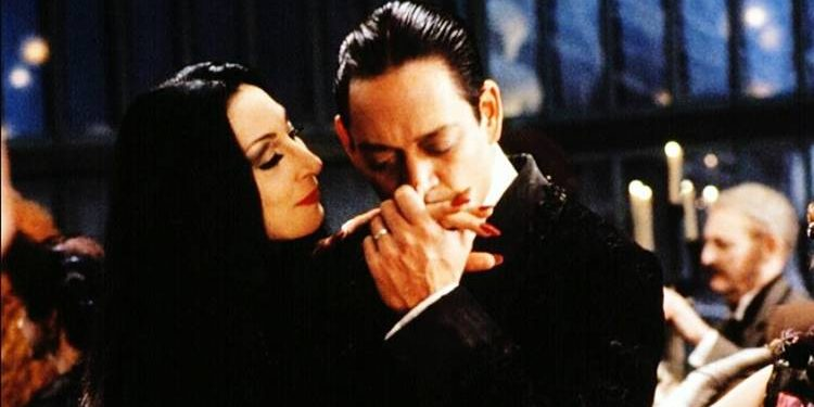 Gomez Addams kisses his wife Morticia's hand   gtg
