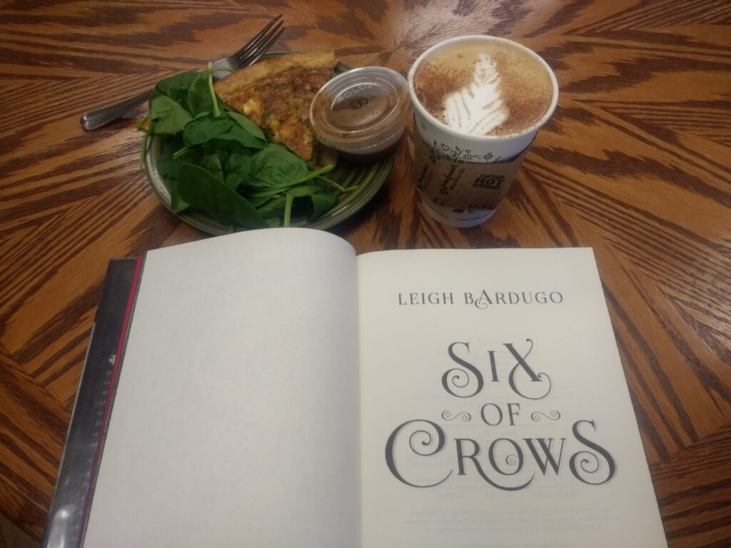 Six of Crows by Leigh Bardugo on a table beside quiche and a latte