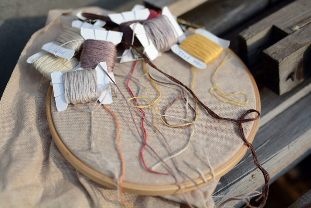 cross stitch hoop and floss on bobbins