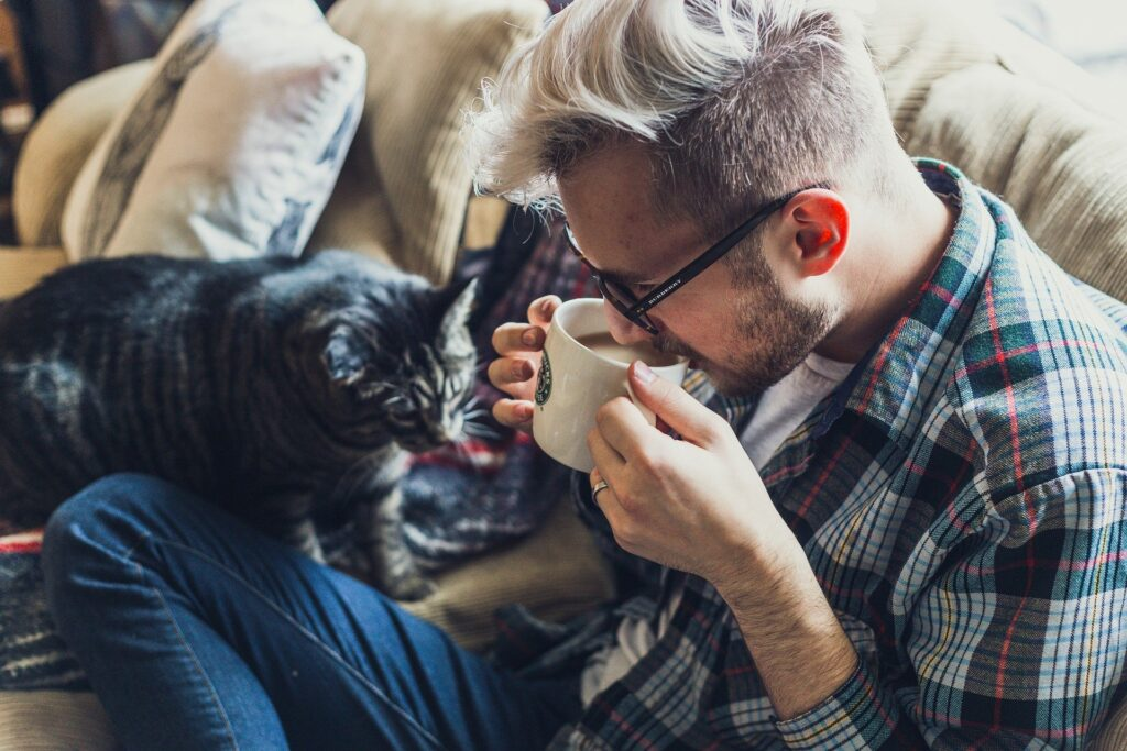man relaxing drinking coffee with cat