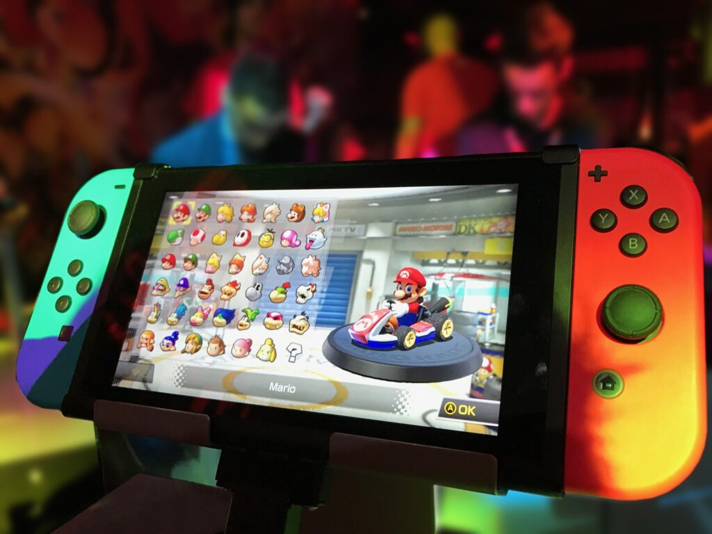 A Nintendo Switch with the image of Mario in a go-cart and several character options beside him
