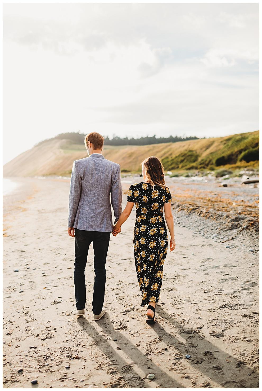 couple walking hand in hand down quiet beach