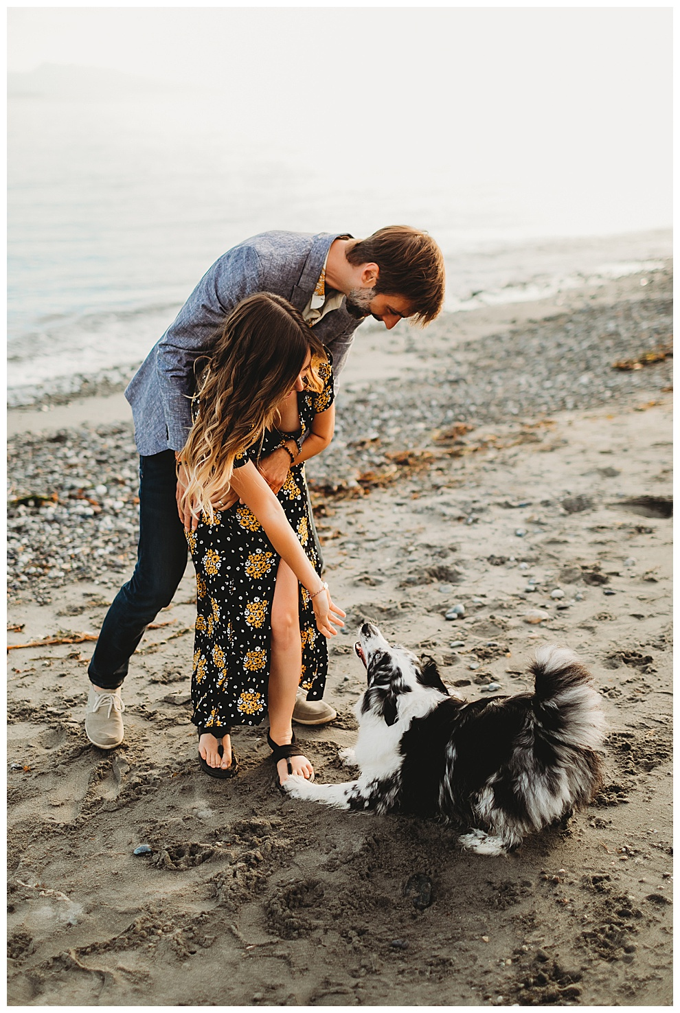 couple hugging on beach as dog sits at their feet