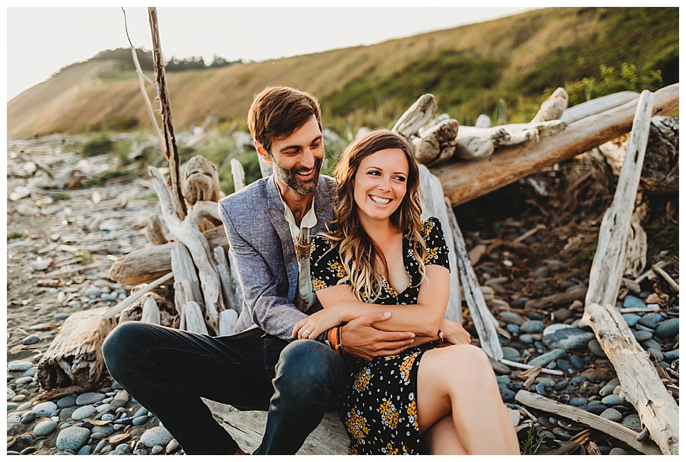 man and woman snuggle on beach during engagement shoot