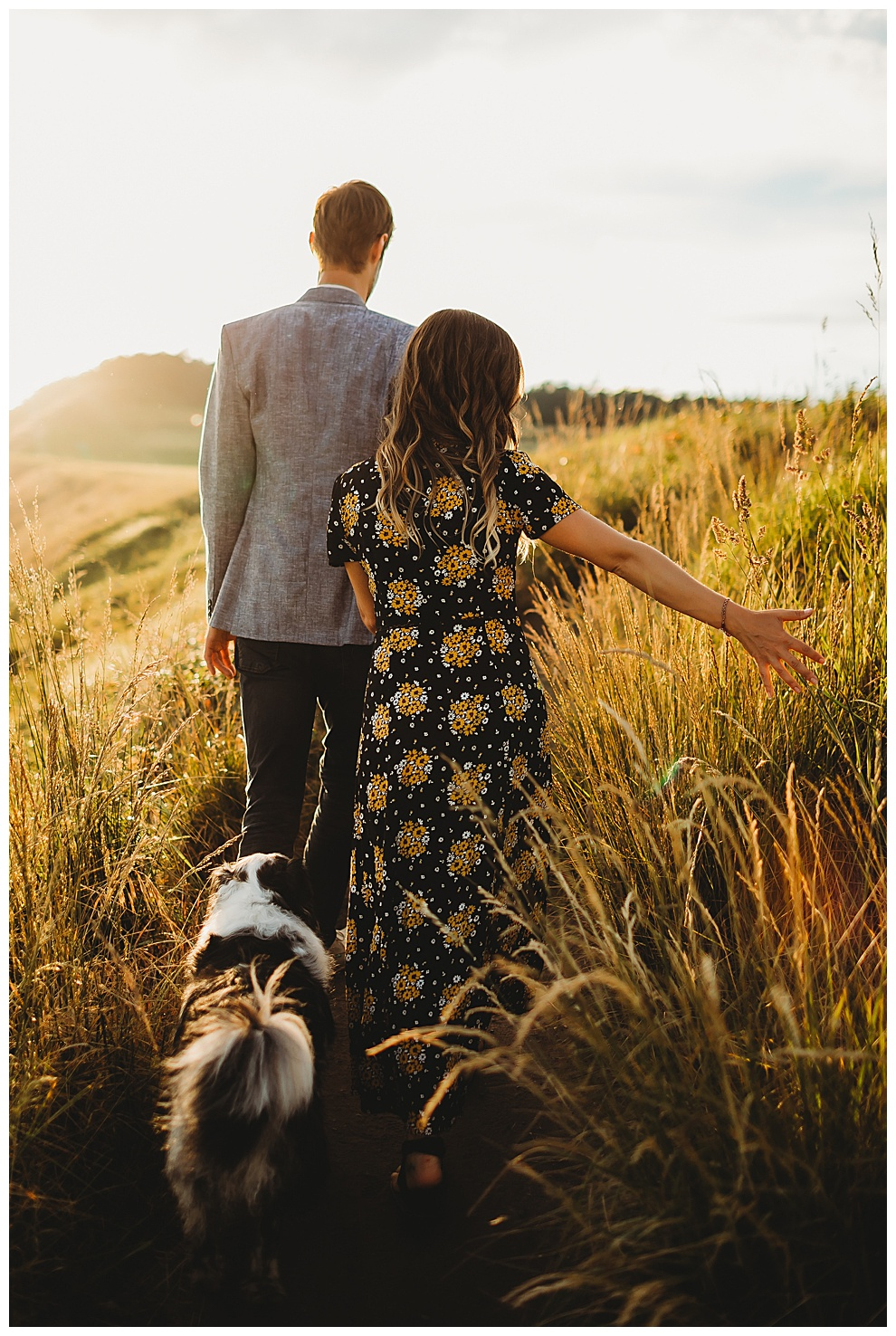 couple walk their dog through tall grass at sunset