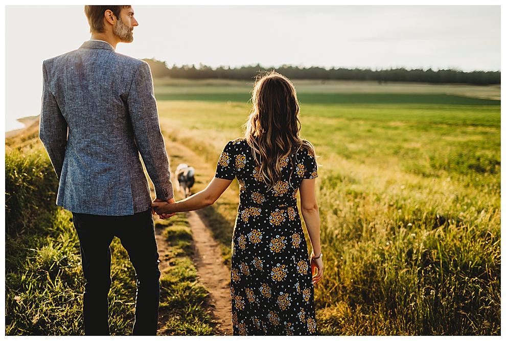 couple walk their dog along grassy path at sunset