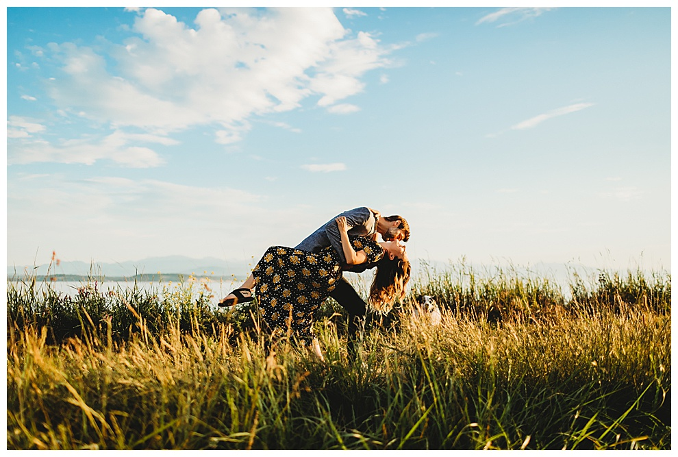 couple kiss passionately in grassy field