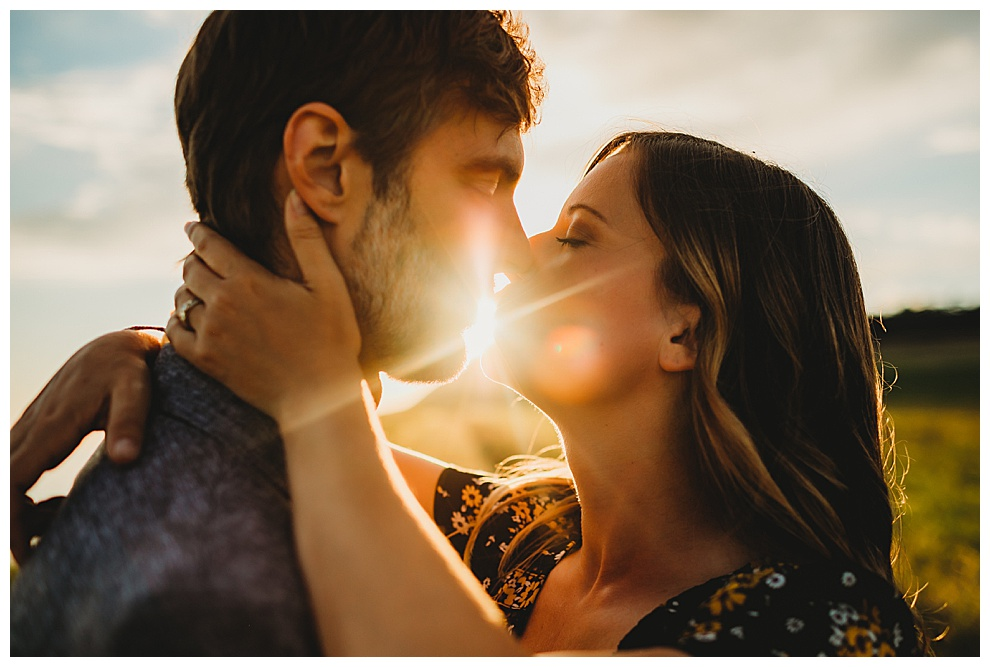 a young couple embrace and kiss at sunset