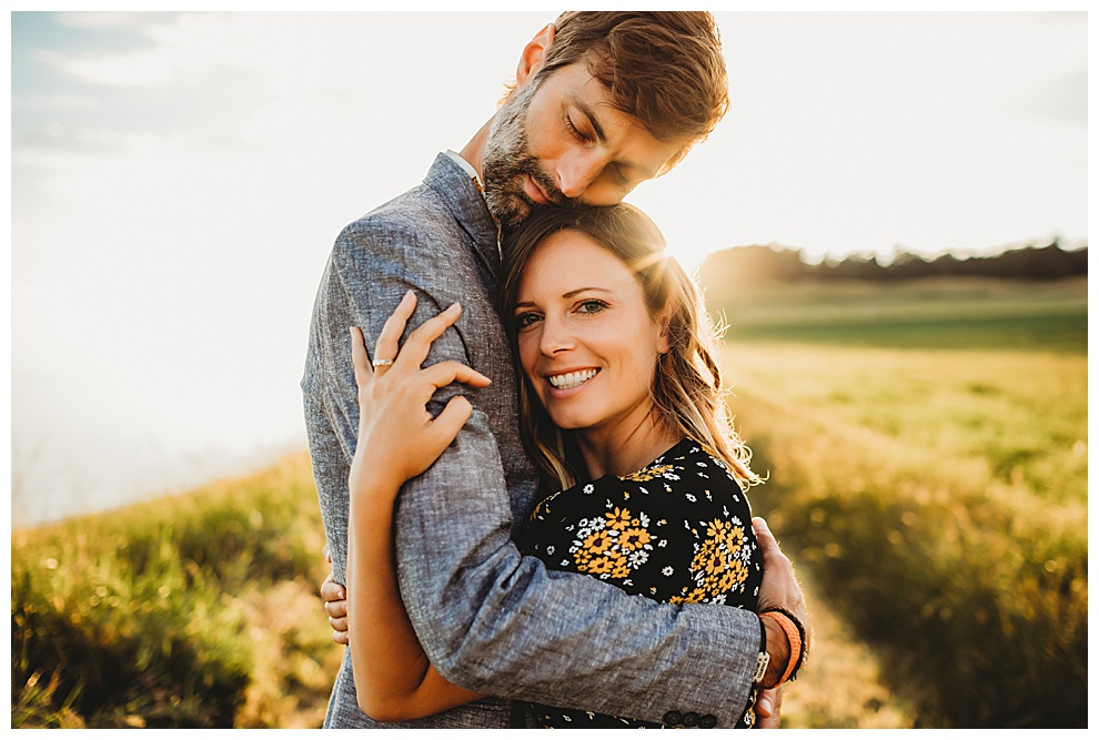 young couple hug during outdoor engagement photoshoot