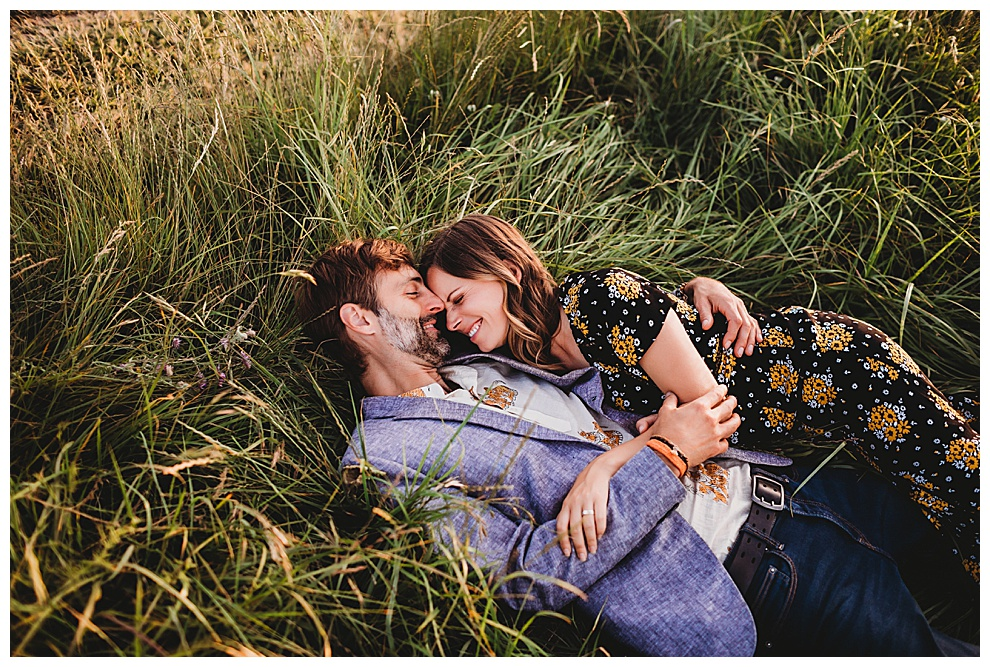 man and woman laughing lying in grass