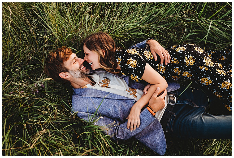 couple lying in grass, hugging and laughing