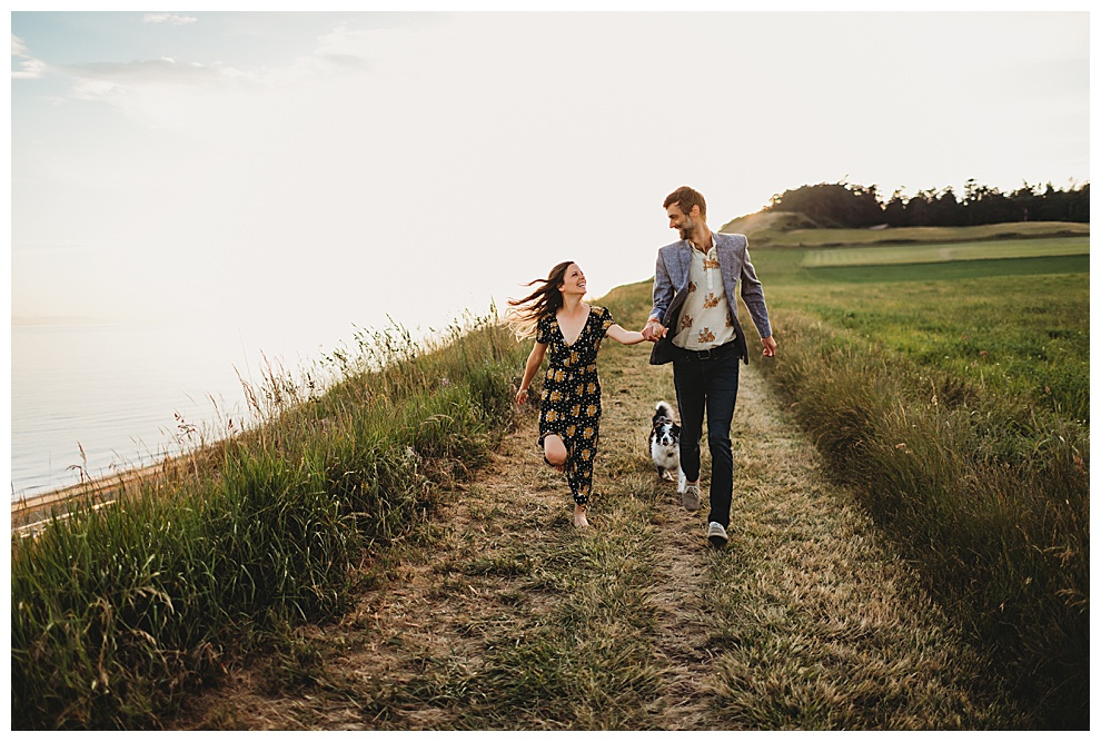 young couple running hand in hand along west coast
