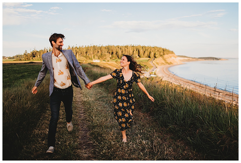 young couple running hand in hand along Whidbey Island coast