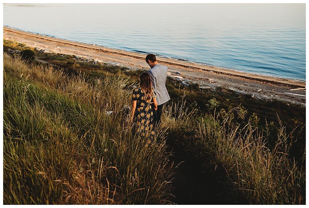 man and woman walk along beach