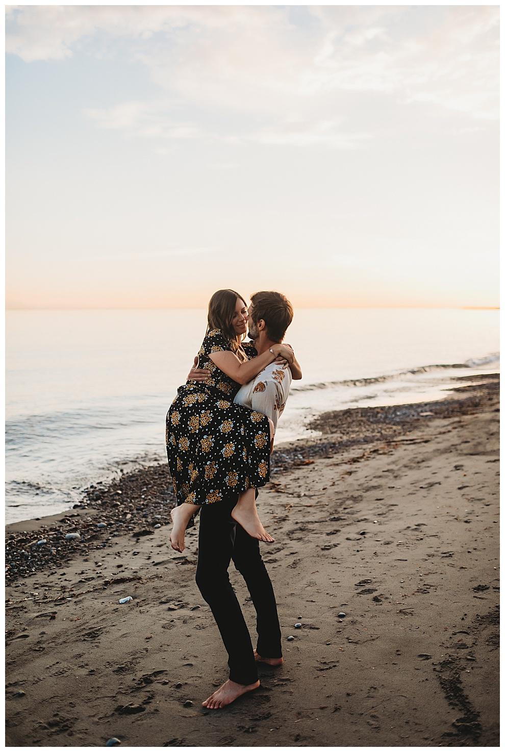 man picks up his girlfriend on beach