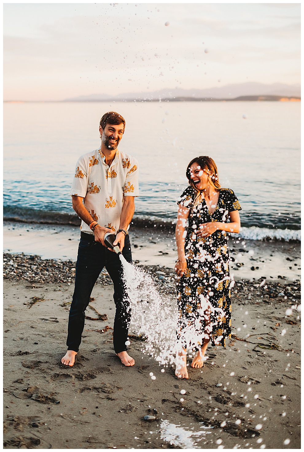 young couple popping bottle of champage on beach