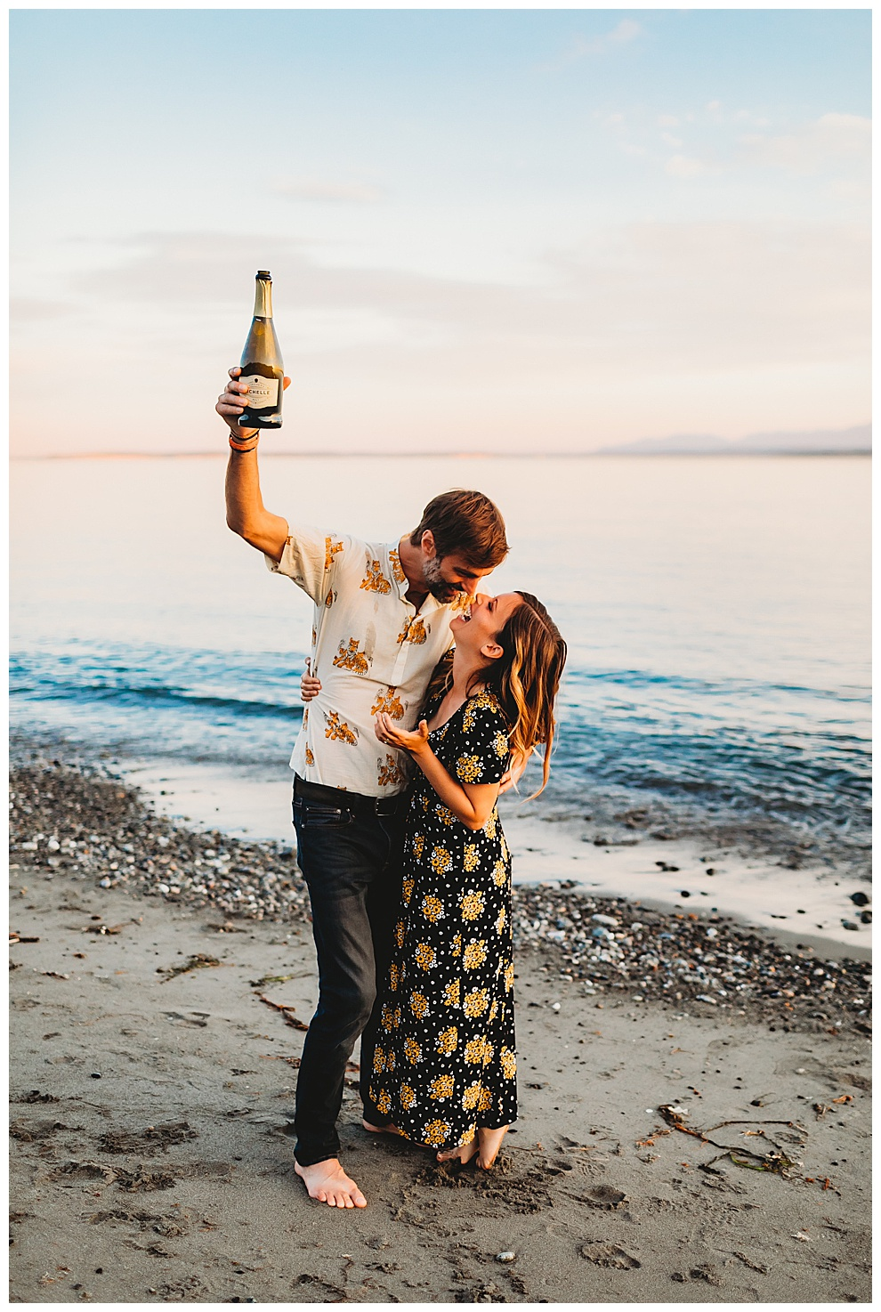 couple kissing and holding champagne on beach