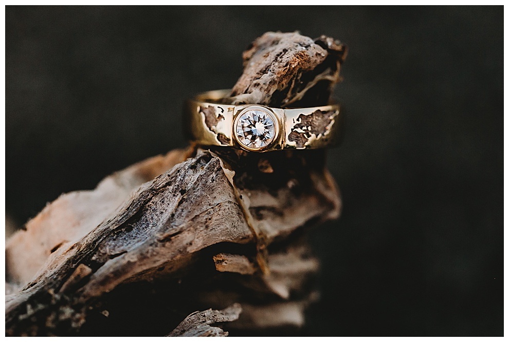 gold engagement ring with single large diamond and engraving of world map