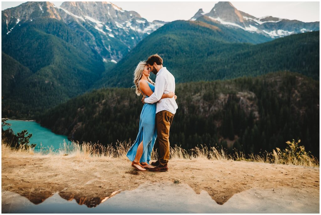 Couple on a mountain getting engagement photos taken