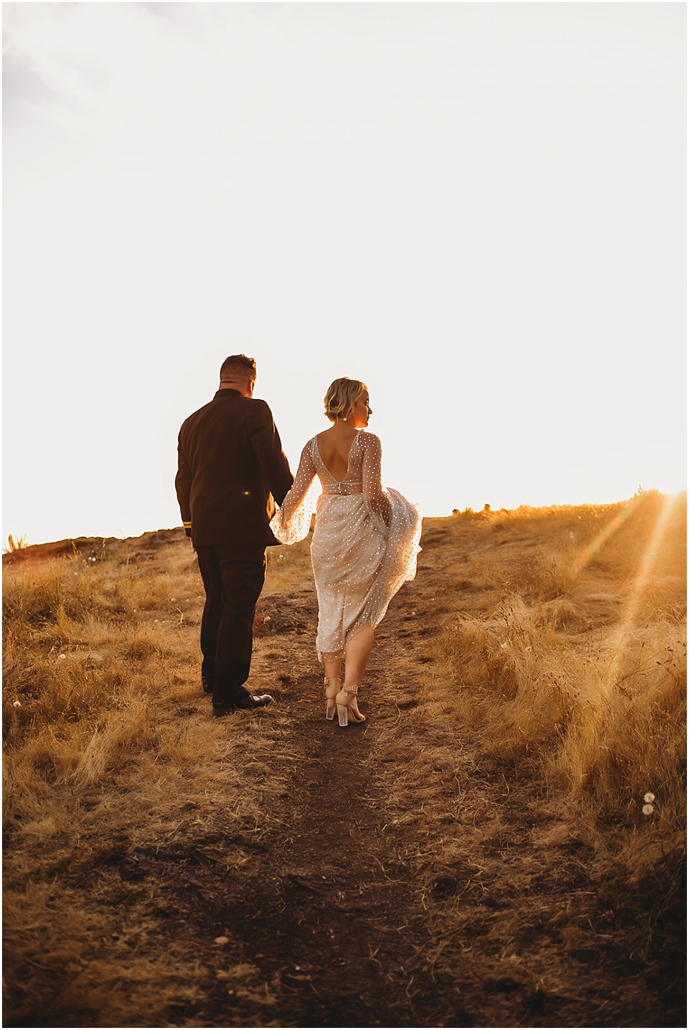 Bride and groom walking in field at sunset