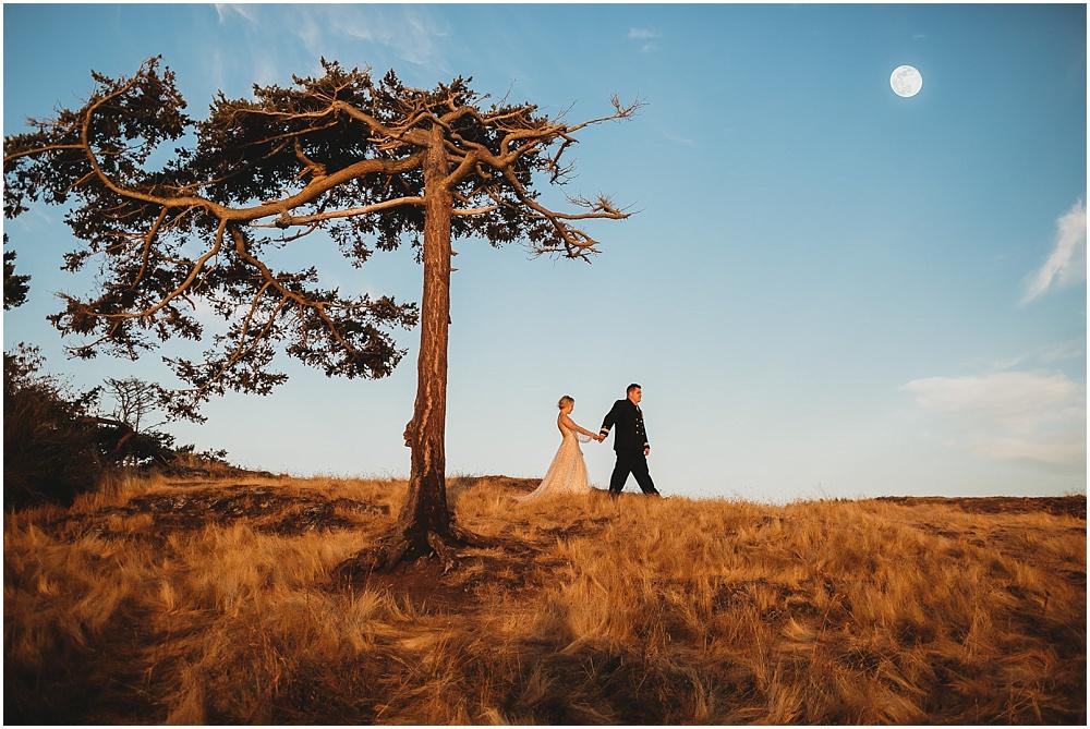 Bride and groom walking under the moon