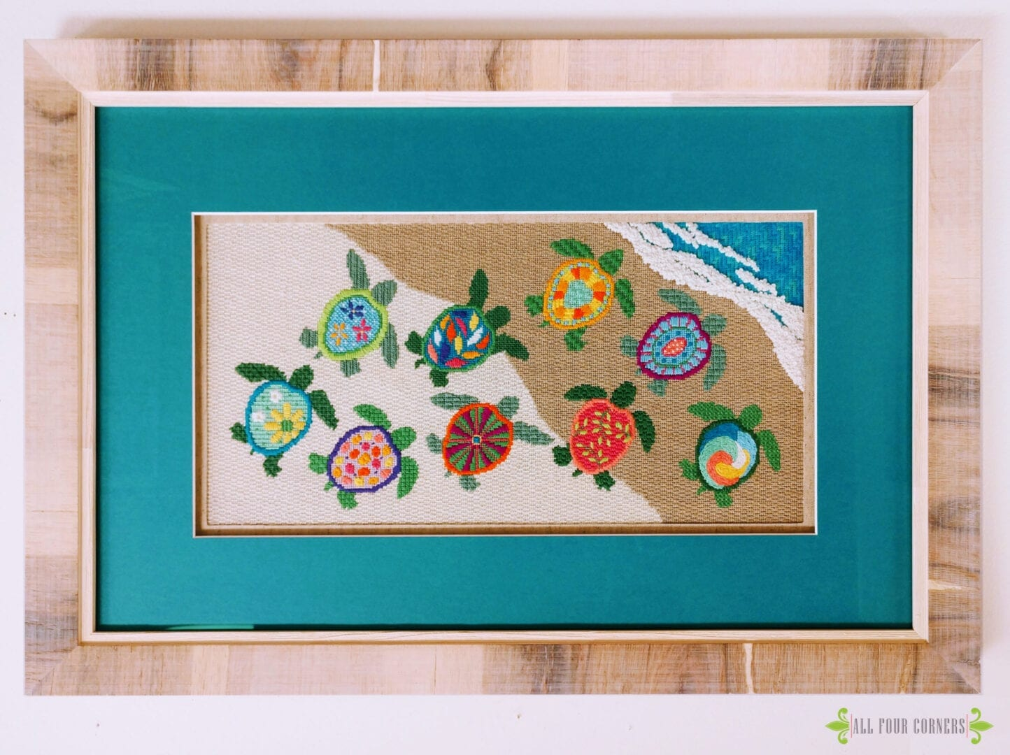 framed turtle needle point with turquoise mat and heavy wood grain frame.