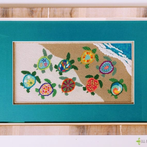 detail of framed turtle needle point with turquoise mat and heavy wood grain frame.