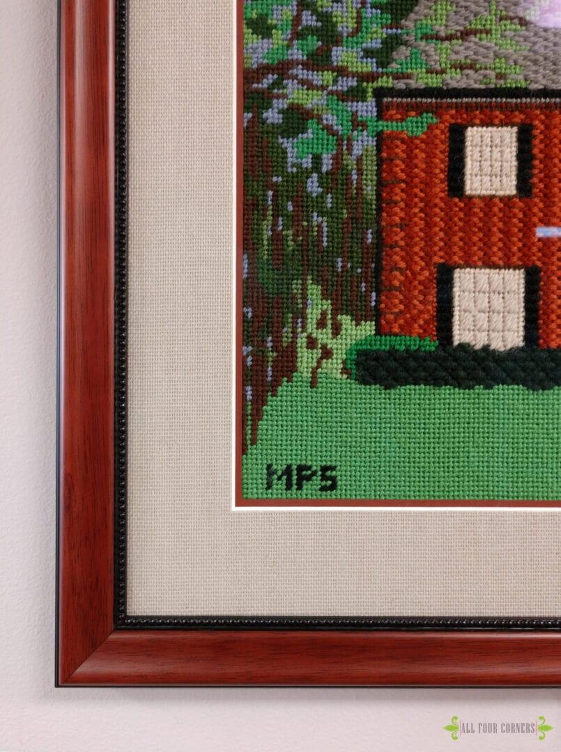 detail of framed needlepoint framed in wood