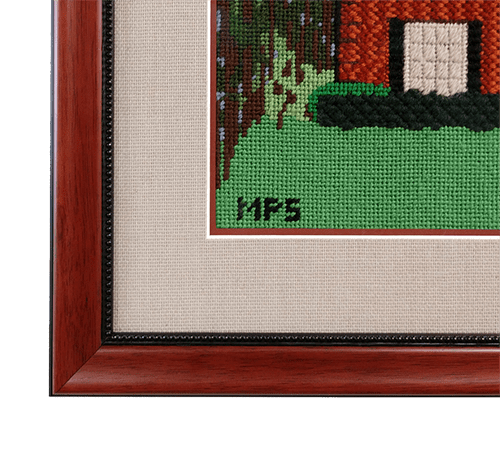 detail of home needlepoint in wooden fram