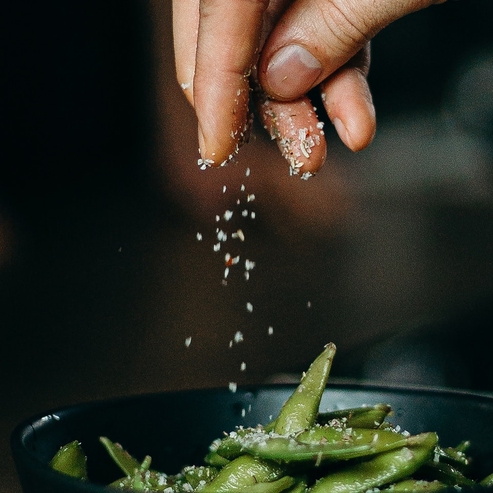 person-pouring-seasoning-on-green-beans-on-bowl-3338497