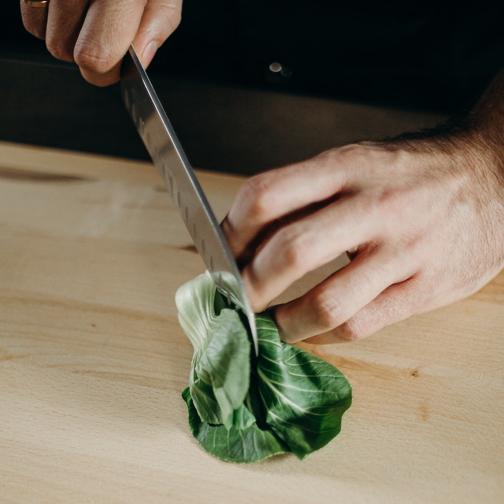 person-slicing-green-leafy-vegetable-3298639