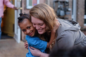 Horton's Kids student and tutor share an embrace