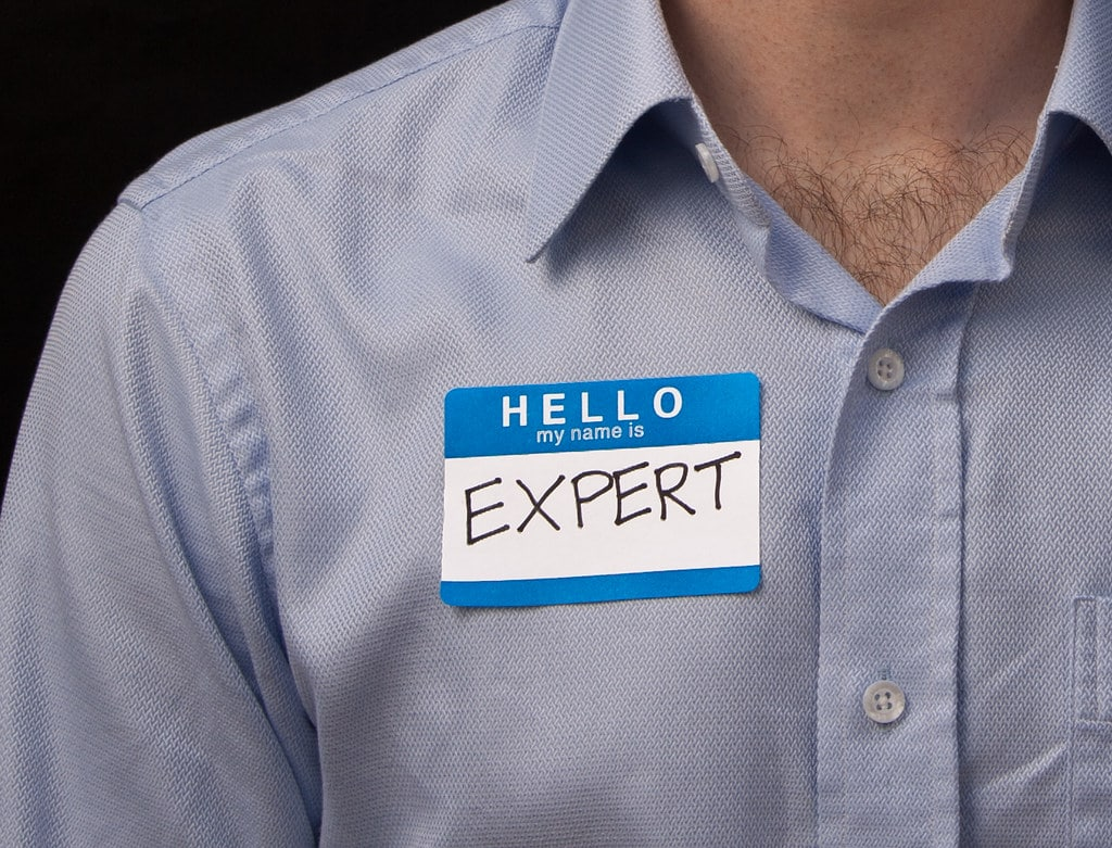 a man in his shirt and expert sign