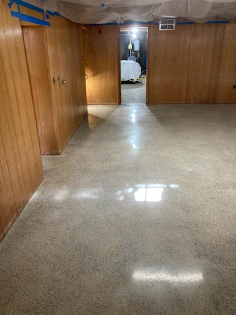 """Basement job in Whitman, MA. The slab had some moisture issues because no vapor barrier was under the slab, and therefore the owner removed the VCT. We started by grinding off the residual adhesives. After grinding, the slab was honed and densified. The slab was polished to an 800 grit finish. A guard was applied and the slab was burnished. You may see """"ghosting"""" in the polished concrete after the VCT had been removed."""