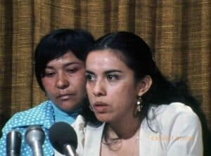 Two women are seated behind microphones. The woman in front is wearing a white jacket.