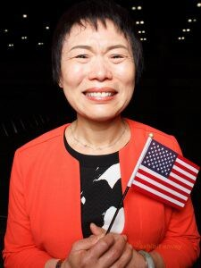 A Chinese woman holds a small American flag while crying happy tears.