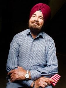 A man in a turban and a blue shirt leans back and smiles at the camera.