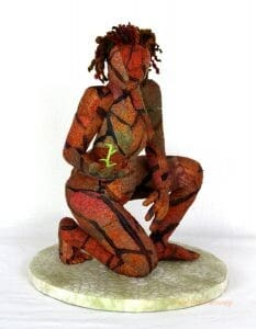 A sculptural textile artwork depicts a woman with parched, orange and black skin holding a small green sprout.