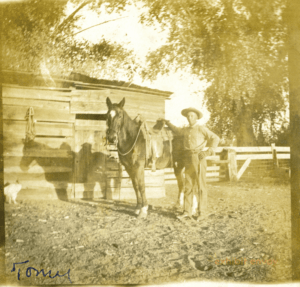 A farm hand stands to the right of a horse and in front of a wood building in a sepia-toned photograph.