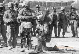 A soldier kneels in front of two rifles standing upright. Helmets are perched on the butt of each rifle. Other soldiers stand nearby.