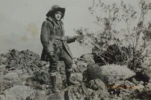 A woman stands on rocks outside. She has a stern expression on her face, wearing men's clothing, and has a visible sidearm.