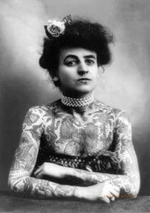 A woman stares defiantly at the camera. She is heavily tattooed and her arms are crossed.