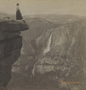 A woman stands at the edge of a cliff in Yosemite National Park in a sepia-toned photograph.