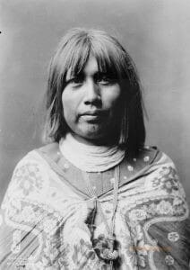A Native woman looks at the camera. She has lines tattooed on her chin.