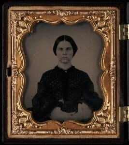 A woman stares straight-faced at the camera. She has lines tattooed on her chin. The photograph is in a gold frame, also seen in the image.