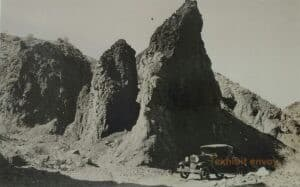 An old car is pictured in front of large rock formations.